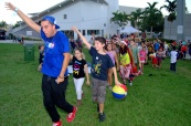 Rapper Sean Olivera leads kids in a conga line.