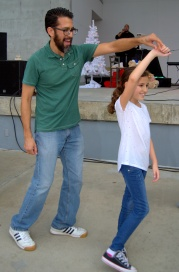 A dad twirls his little girl.