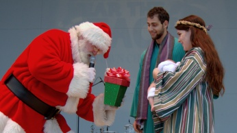 . . . and gives the first gift of the season to the Holy Family.