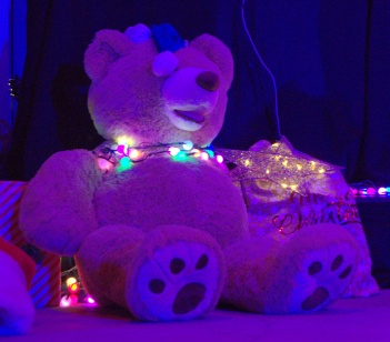 As night falls, a large teddy bear on the stage takes on a magical hue . . .