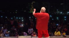 Santa returns once more to lead the crowd in Silent Night, using their cellphones as candles.
